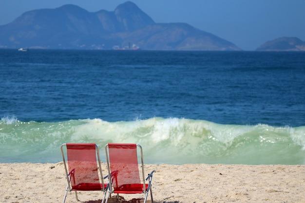 Deux des chaises de plage rouges sur la plage de copacabana contre les vagues déferlantes de l'océan, rio de janeiro