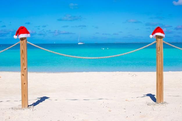 Deux chapeaux de père noël sur la clôture à la plage blanche tropicale