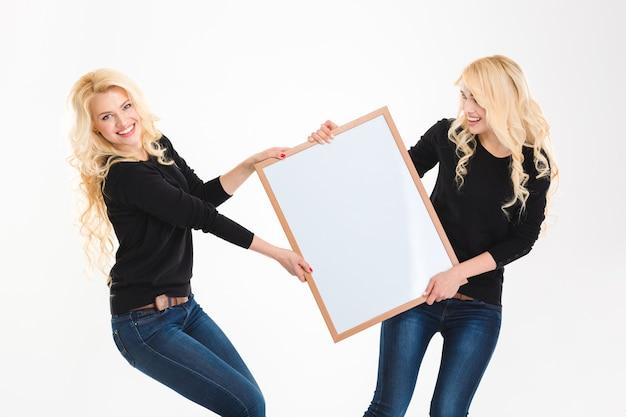 Deux charmantes jeunes soeurs blondes jumelles s'amusant tenant un tableau blanc sur fond blanc