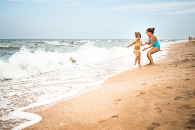 Deux charmantes petites filles en maillot de bain dansent sur une plage de sable près de la mer contre le ciel bleu par une chaude journée d'été. concept de vacances avec enfants