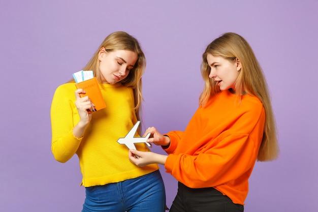 Deux charmantes sœurs jumelles blondes vêtues de vêtements colorés détiennent un passeport, un billet d'embarquement, un avion en papier isolé sur un mur bleu violet. concept de mode de vie familial de personnes.