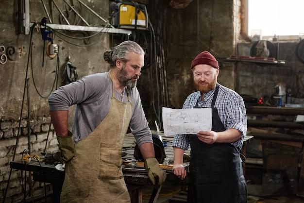 Deux charpentiers examinant le plan d'un nouveau produit ensemble en équipe pendant leur travail en atelier