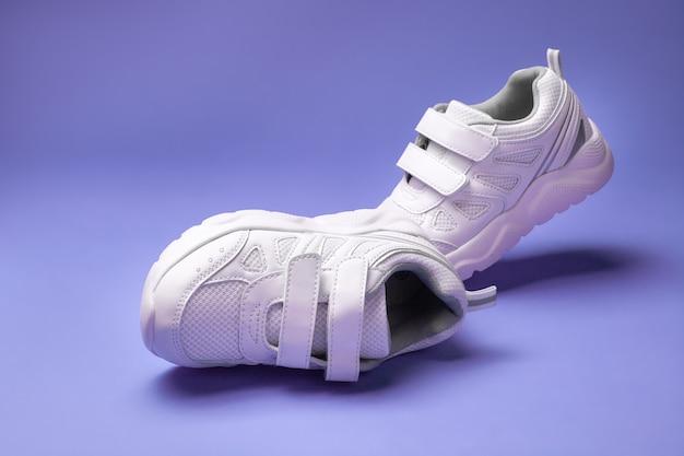 Deux chaussures de course pour enfants blanches avec fermetures velcro pour des chaussures faciles pour enfants isolées sur un fond mauve ...