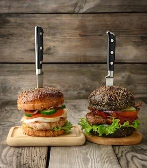 Deux cheeseburgers avec légumes et steak de viande sur une planche de bois, un sandwich est percé d'un couteau