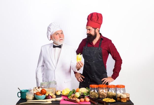 Deux chefs culinaires professionnels se tiennent près de la table avec des chefs d'hommes barbus de légumes en uniforme prêt