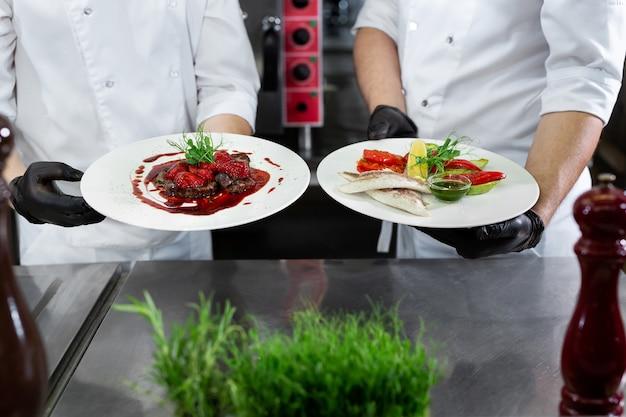 Deux chefs dans une cuisine professionnelle tiennent des plats préparés dans leurs mains