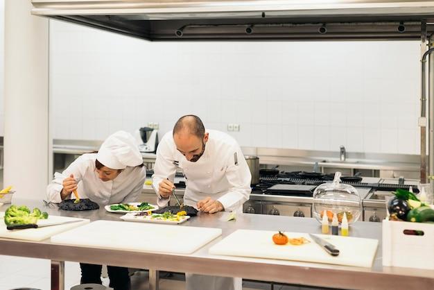 Deux chefs professionnels cuisinant ensemble dans une cuisine.