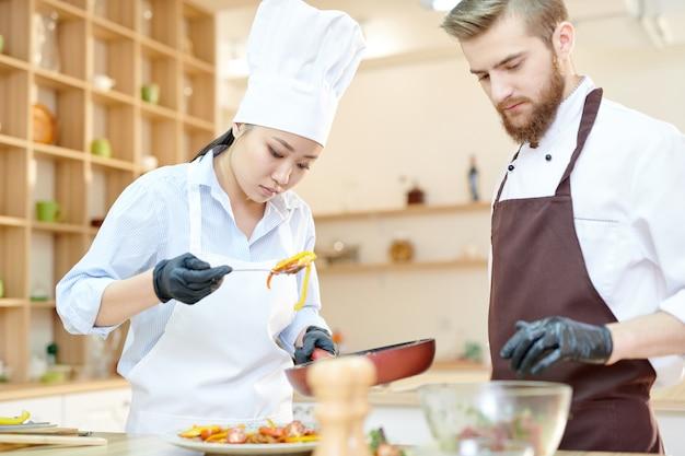 Deux chefs travaillant dans une cuisine moderne