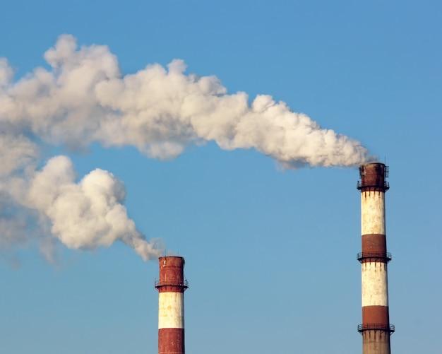 Deux cheminées d'usine avec des nuages de vapeur ou de fumée dans le ciel bleu. pollution environnementale.