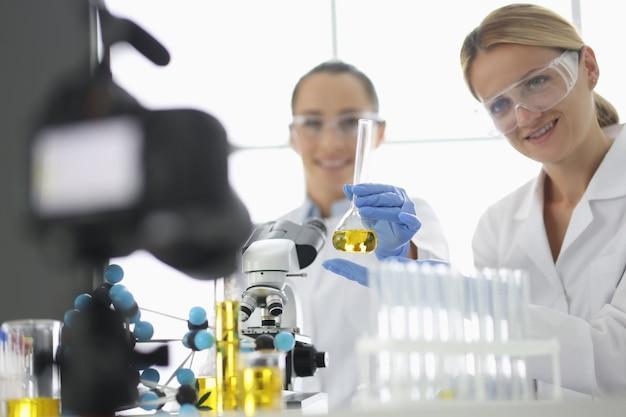 Deux chercheurs filment des expériences en laboratoire devant une caméra