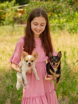 Deux chiens dans les bras d'une adolescente. chien chihuahua. chihuahua noir et blanc.