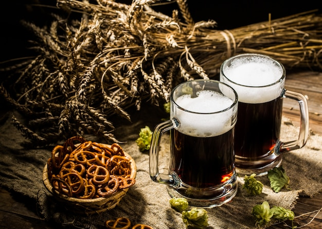 Deux chopes de bière avec du blé et du houblon, un panier de bretzels