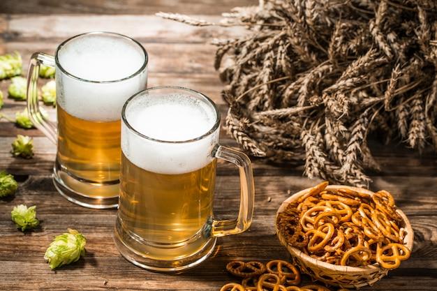 Deux chopes de bière, des pointes, hop sur une table en bois