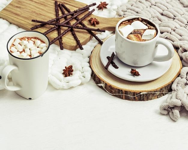 Deux chopes de chocolat chaud à la guimauve décorées sur du bois blanc