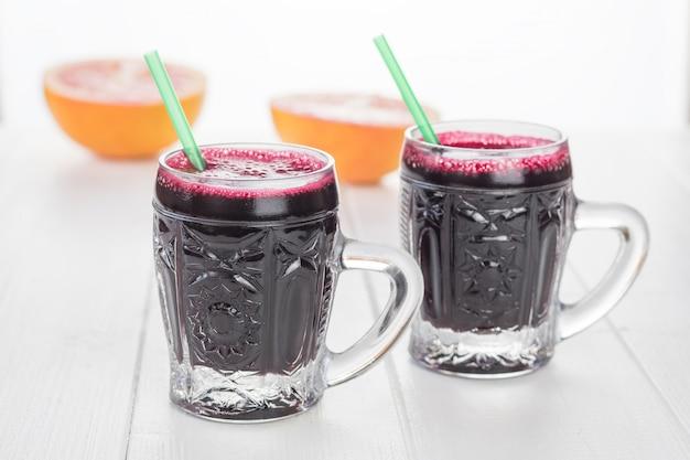 Deux chopes en verre avec du jus de pamplemousse et de la betterave sur une table en bois blanche.