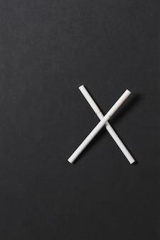 Deux cigarettes blanches croisées comme la lettre x sur fond noir