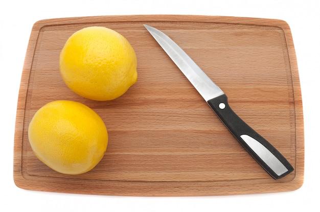 Deux citron frais jaune avec un couteau sur une planche à découper en bois.