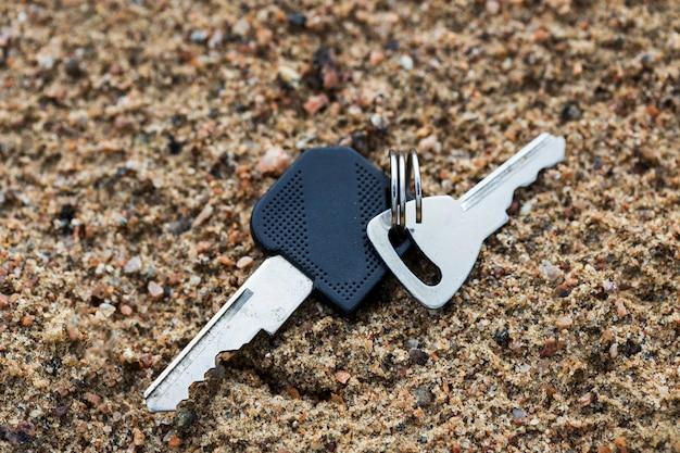 Deux clés reposent sur le sable. perte des clés de la maison. photo de haute qualité