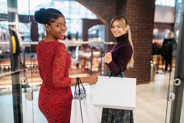 Deux clientes avec des sacs à provisions au centre commercial.