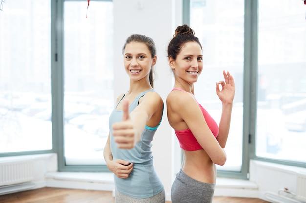 Deux clients heureux posant dans une salle de sport