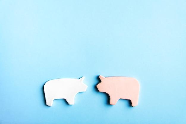 Deux cochons d'argile faits à la main sur fond pastel doux, carte de saint-valentin ou éléments de conception d'affiches.