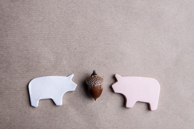 Deux cochons d'argile faits à la main avec gland sur fond de papier kraft, carte de saint-valentin ou éléments de conception d'affiches.