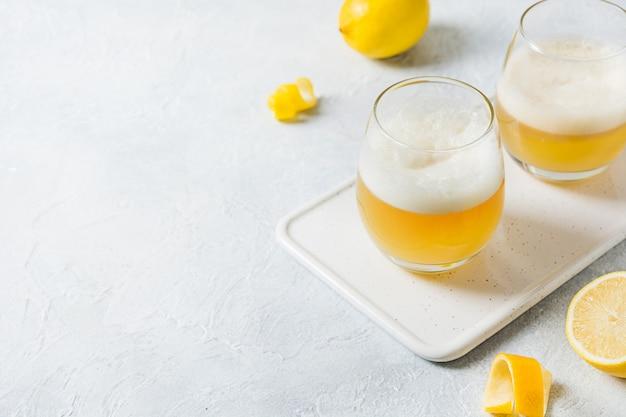 Deux cocktails aigus de whisky avec des ingrédients, du jus de citron, du sirop de sucre et du blanc d'oeuf en verre blanc. orientation horizontale.