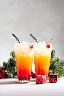Deux cocktails alcoolisés sunrise avec tequila se tiennent près de branches de sapin sur fond gris