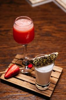 Deux cocktails au citron vert et fraise sur la planche de bois