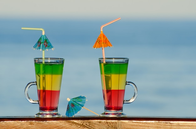 Deux cocktails avec des pailles sur le bar au bord de la mer au loin