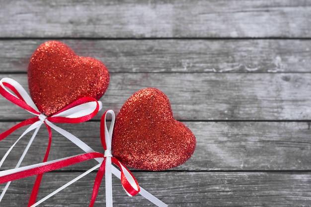 Deux coeur rouge brillant avec des arcs sur une table en bois