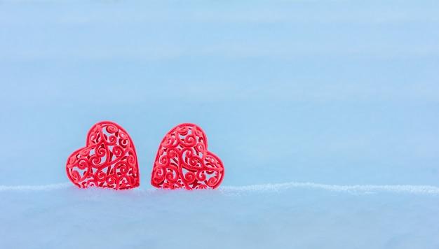 Deux coeur de velours rouge dans une congère. concept de la saint-valentin