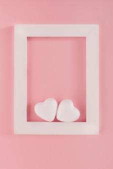 Deux coeurs blancs dans un cadre blanc sur fond rose