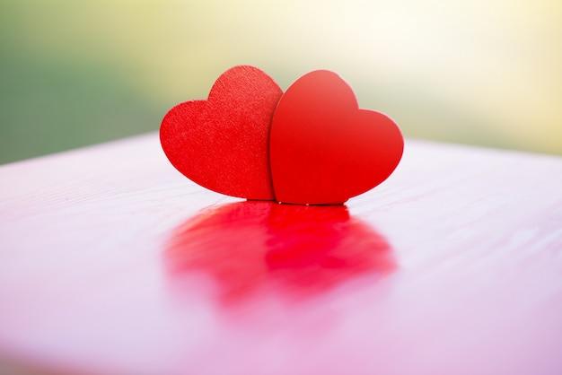 Deux coeurs en bois sur une table en bois rouge floue, expression d'amour, festival de la saint-valentin, concept d'amour