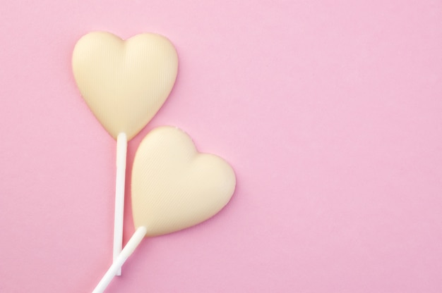 Deux coeurs de bonbons au chocolat blanc sur rose