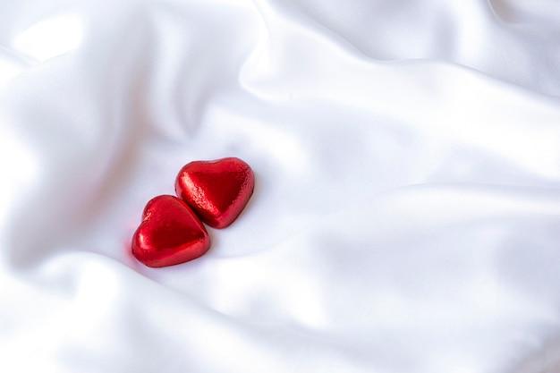 Deux coeurs de bonbons rouges sur un tissu de soie blanche, décoration festive, st. saint valentin, jour de la femme, célébration de mariageconcept, place pour le texte, mise à plat