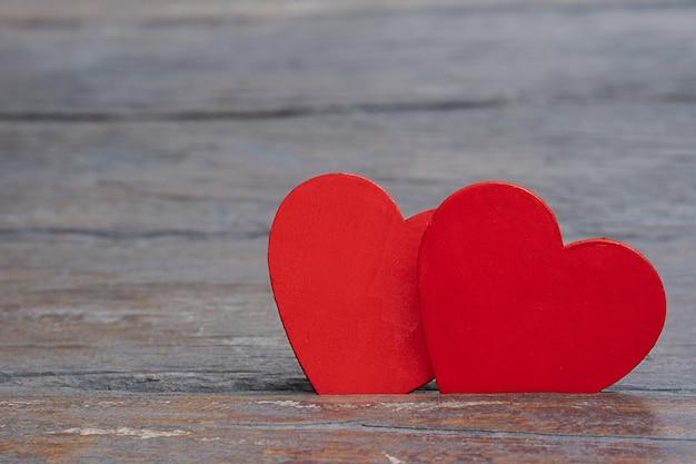 Deux coeurs sur le fond sombre. couple de coeurs différents rouges et blancs sur la surface en bois