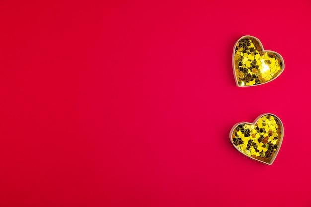 Deux coeurs d'or avec des confettis sur une surface rouge pour la saint valentin. espace pour le texte. bannière web ou carte de voeux