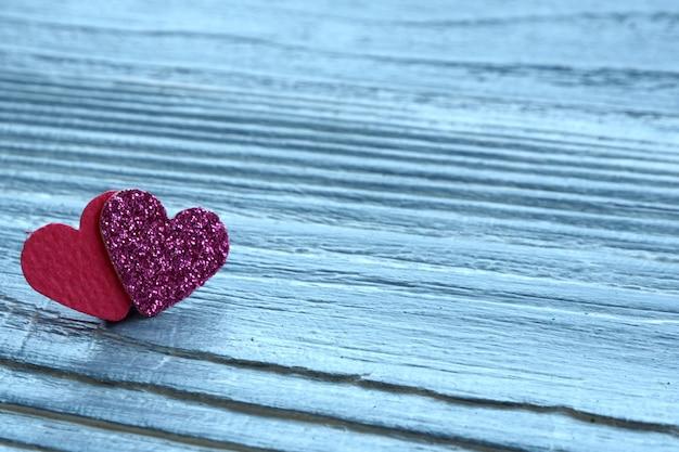 Deux coeurs paillettes rose et rouge sur un fond en bois gris