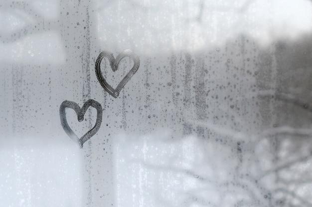 Deux coeurs peints sur un verre embué en hiver