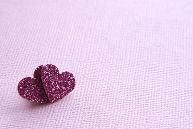 Deux coeurs roses brillants sur un fond de texture rose