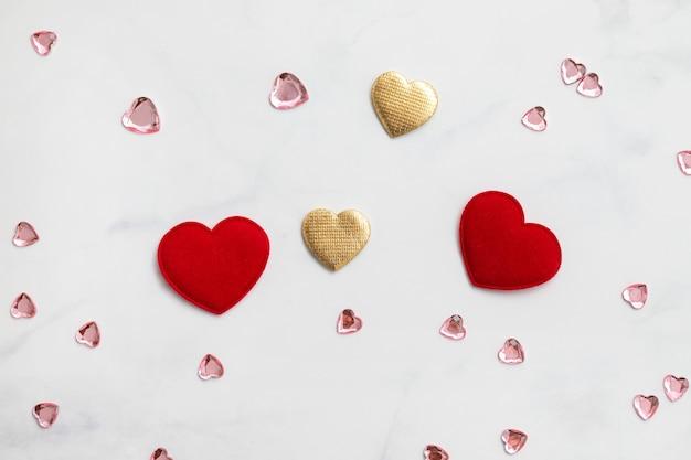 Deux coeurs rouges et coeurs dorés sur fond gris