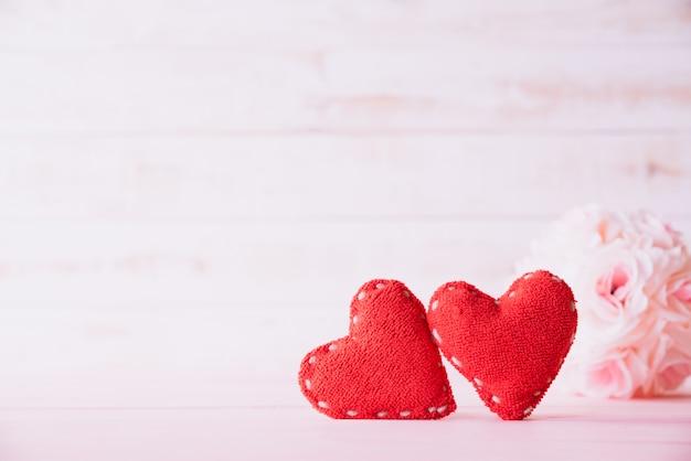 Deux coeurs rouges avec une fleur rose rose sur fond en bois.