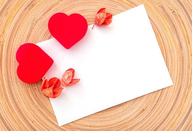 Deux coeurs rouges et fleurs sèches sur feuille blanche, mise en page, espace pour le texte. carte postale pour la saint-valentin ou la célébration de mariage