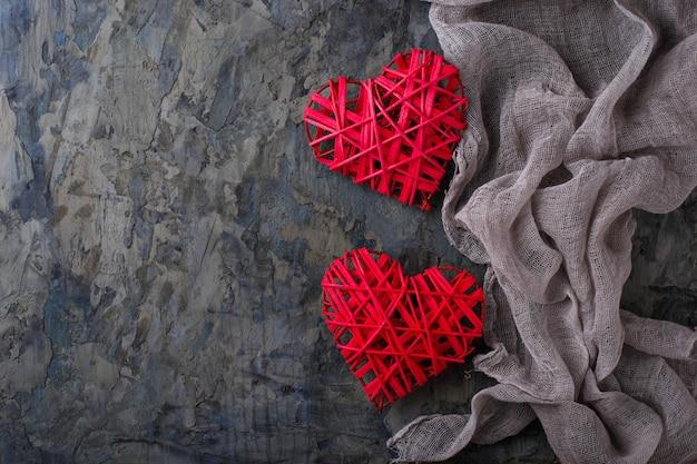 Deux coeurs rouges sur fond de béton, vue de dessus