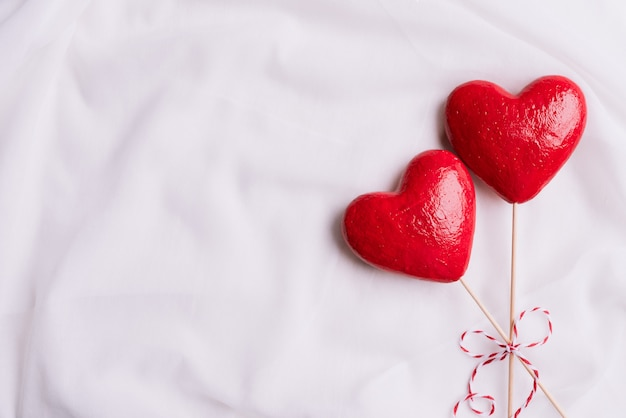 Deux coeurs rouges à la main avec ruban rouge sur fond de tissu blanc.