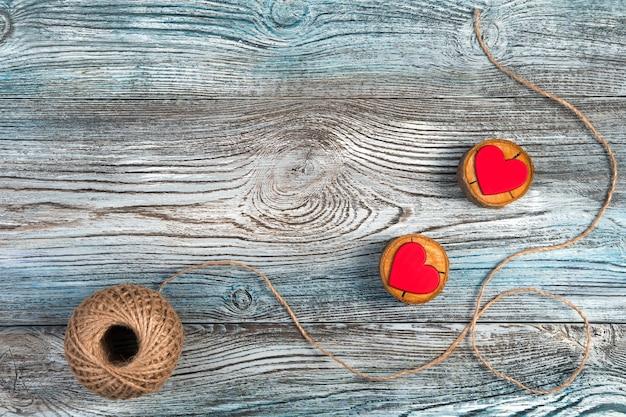 Deux coeurs rouges sur des supports en bois avec du fil de jute sur un fond gris-bleu en bois.