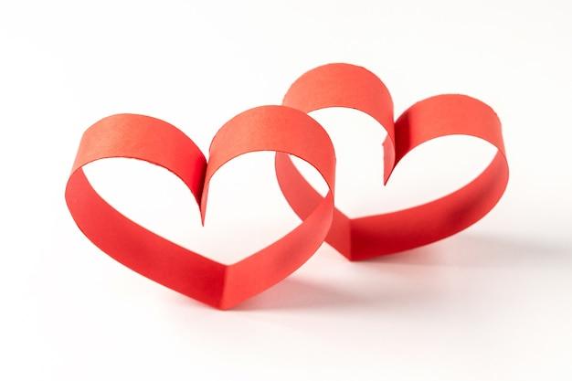 Deux coeurs en ruban sur fond blanc.