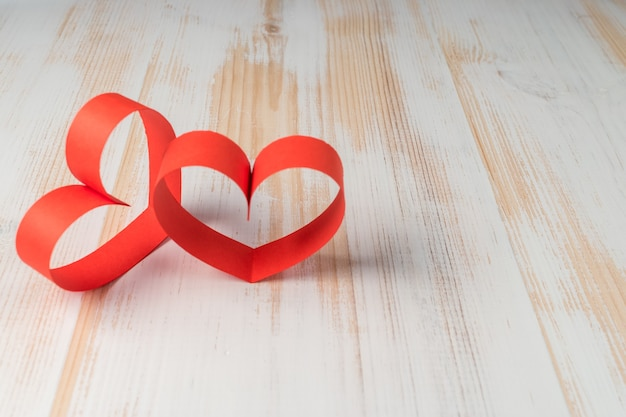 Deux coeurs en ruban sur fond en bois.