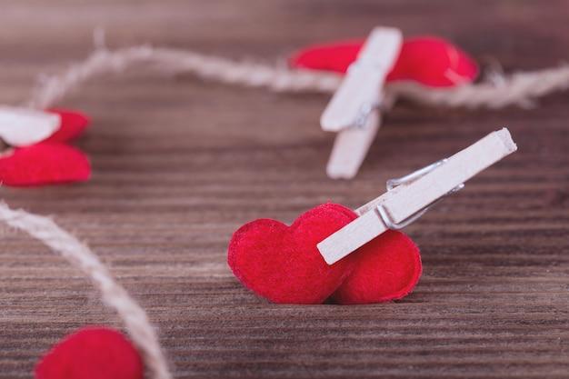 Deux coeurs en textile rouge reliés par une pince à linge. concept de l'amour
